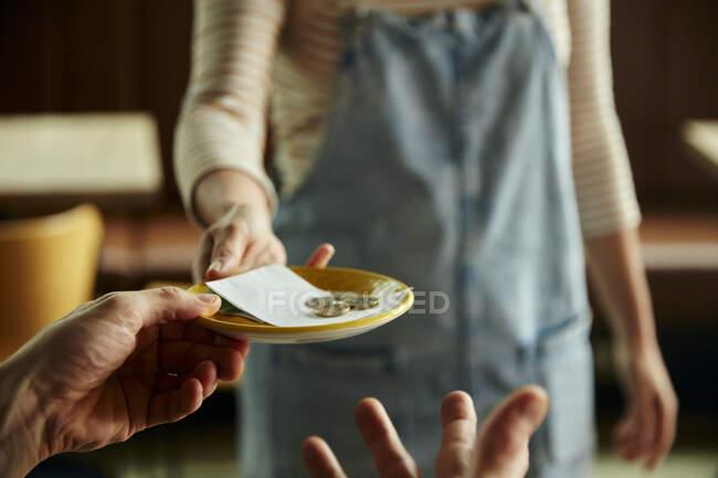 Mujer sosteniendo un plato con un billete de café y monedas. - foto de stock