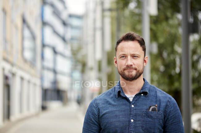Людина з бородою стоїть на вулиці в місті на тихій вулиці — стокове фото