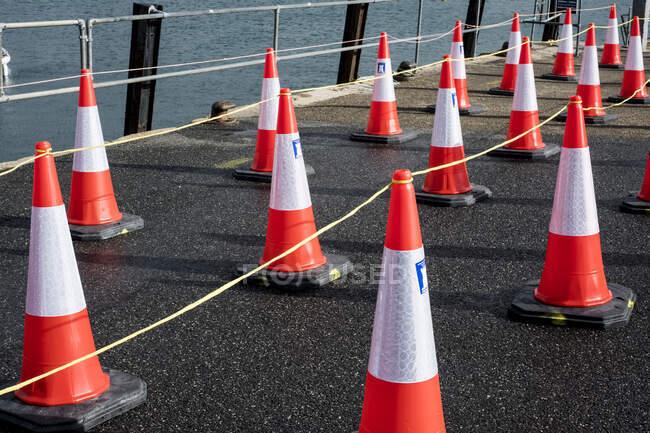 Primer plano de un gran número de conos de tráfico alineados en una pared portuaria. - foto de stock
