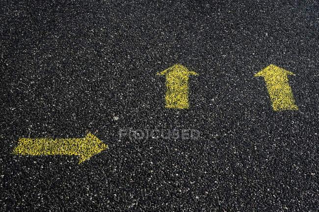 High angle close up of yellow arrow symbols painted on asphalt ground. — Stock Photo