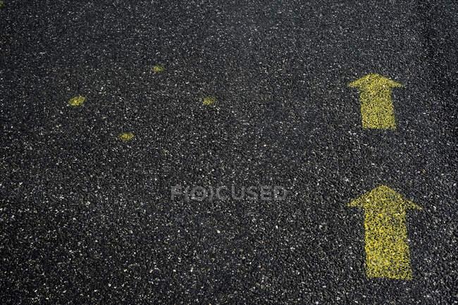 Alto ángulo de cerca de los símbolos de flecha amarilla pintados en el suelo de asfalto. - foto de stock