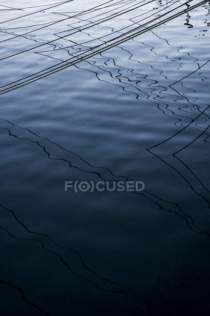 High angle close up of mooring lines and their shadows on the water surface. — Stock Photo
