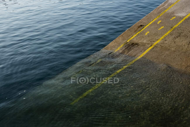 High angle close up of yellow footprints and lines painted on asphalt ground in a harbour. — Stock Photo