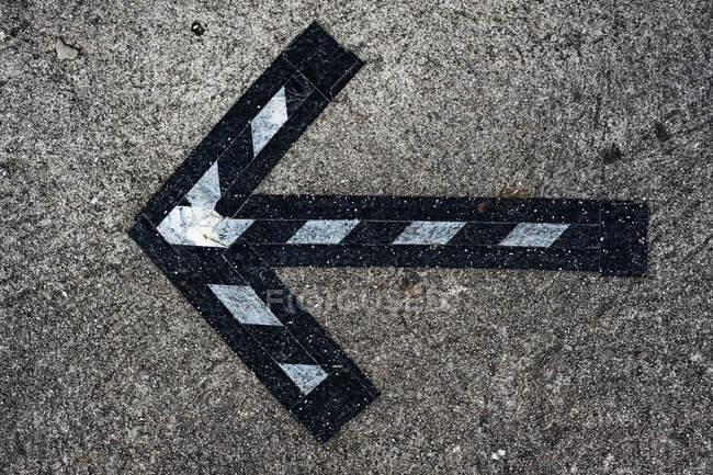 High angle close up of black and white arrow symbol on asphalt ground. — Stock Photo