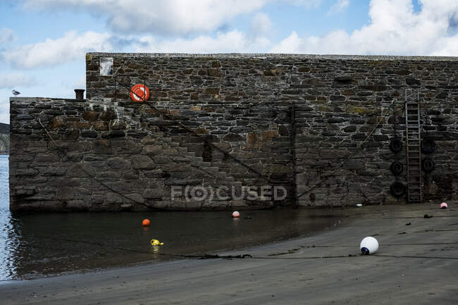 Harbour wall with stairs and buoys on sand at low tide. — Stock Photo