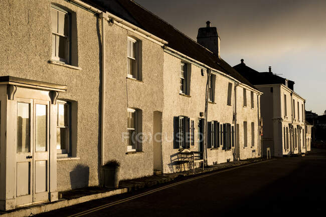 View along narrow terraced houses along a street at sunrise. — Stock Photo