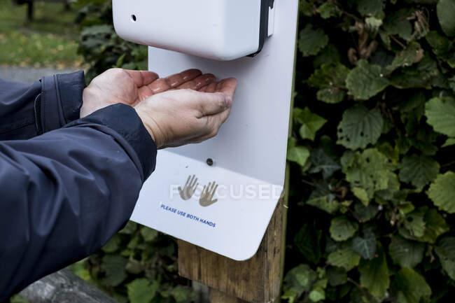 Gros plan de la personne utilisant le distributeur automatique de désinfectant pour les mains pendant la crise du virus Corona. — Photo de stock