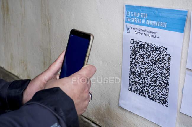 Primer plano de la persona con el código QR de escaneo de teléfonos inteligentes en conjunto con la aplicación Covid-19. - foto de stock