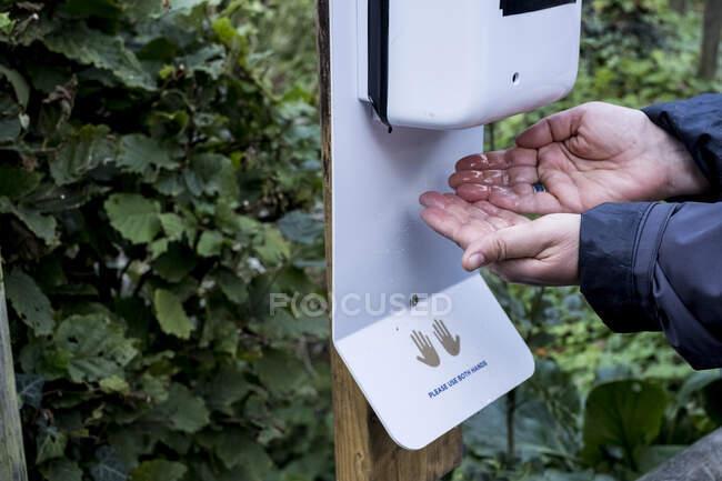 Close-up de pessoa usando dispensador automático de higienizador de mão durante a crise do vírus Corona. — Fotografia de Stock