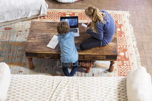 Visão aérea da menina adolescente e seu irmão mais novo usando laptop e telefone inteligente — Fotografia de Stock