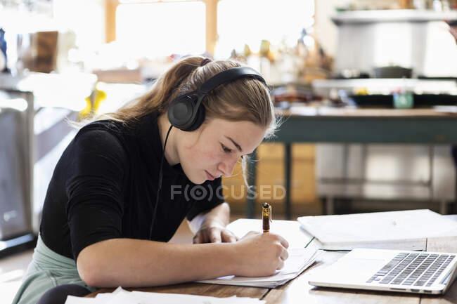 Adolescente portant des écouteurs à l'aide d'un ordinateur portable et écrivant dans un carnet — Photo de stock