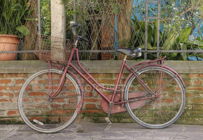Bicicleta apoyada contra la pared. - foto de stock