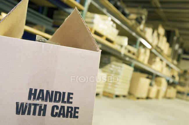 Картонная коробка на складе с полками позади. — стоковое фото