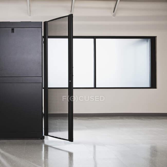 Компьютерный серверный шкаф с открытой дверью и окном в офисе — стоковое фото