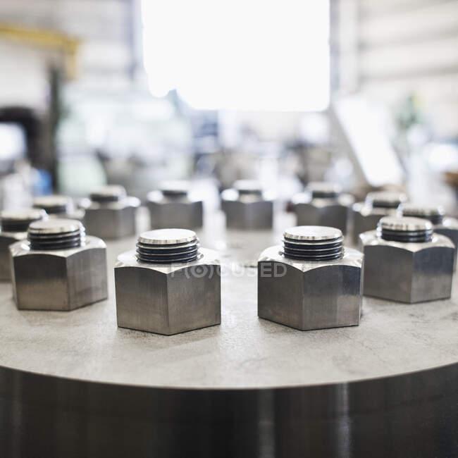 Tuercas y pernos en cilindro en taller - foto de stock