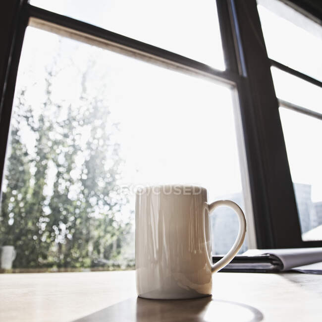 Tazza sulla scrivania in ufficio urbano — Foto stock