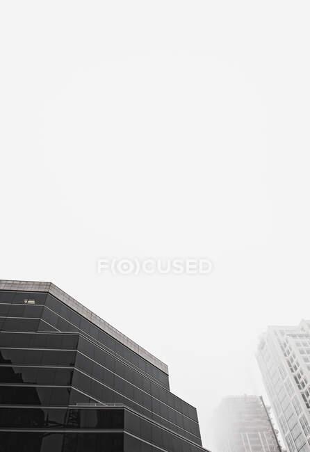 Vista de ángulo bajo de edificios urbanos de gran altura - foto de stock