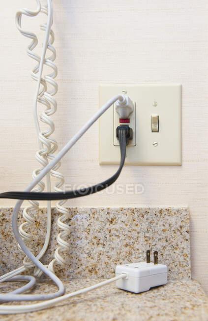 Câbles branchés sur une prise ou une prise électrique et câble téléphonique. — Photo de stock