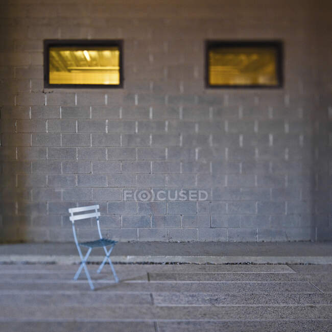 Folding chair in front of concrete block wall. — Stock Photo