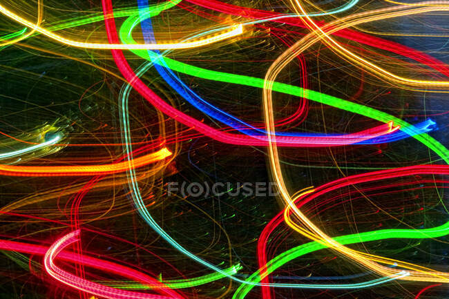 Senderos de luz abstractos sobre fondo oscuro. - foto de stock