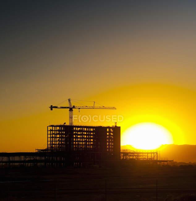 Захід сонця за висотним будівельним майданчиком і краном.. — стокове фото