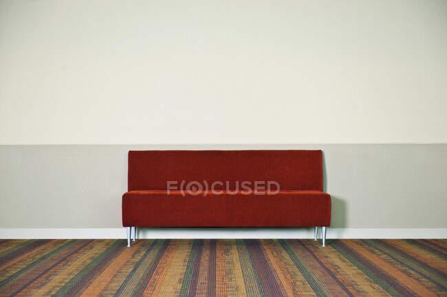 Красный диван на полосатом ковре. — стоковое фото