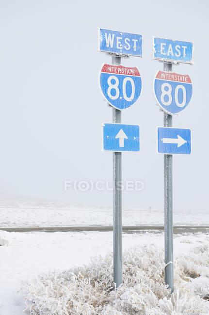 Señalización de la carretera en carretera en un paisaje nevado invernal. - foto de stock