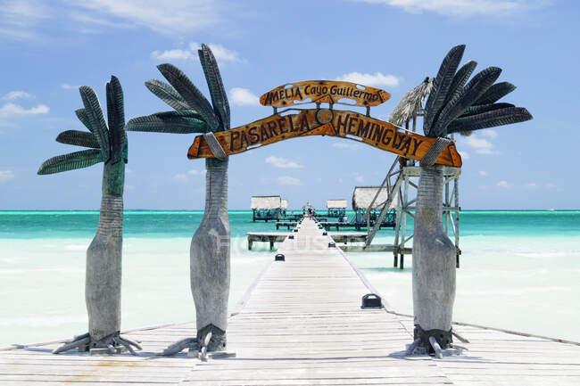 Arco in legno ingresso a un molo nell'oceano tropicale. — Foto stock