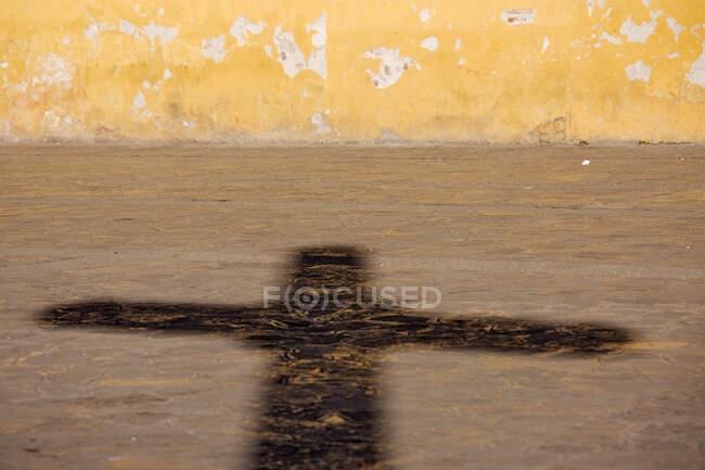 Sombra de un crucifijo en un pavimento de la calle. - foto de stock