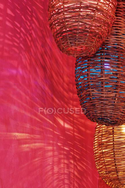 Luminárias de vime fundição sombras na parede vermelha. — Fotografia de Stock