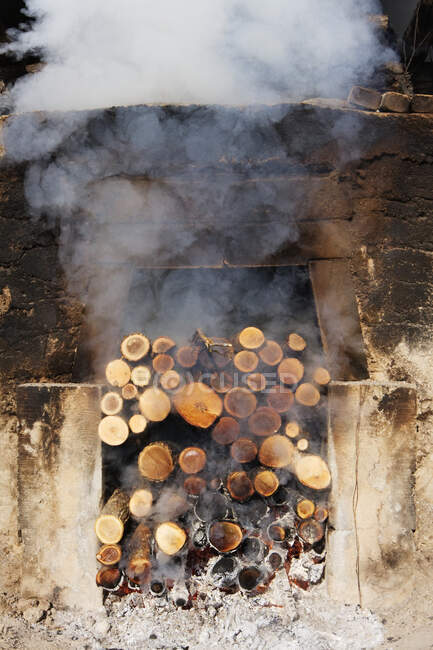 Smoking pile of logs in open fireplace. — Stock Photo