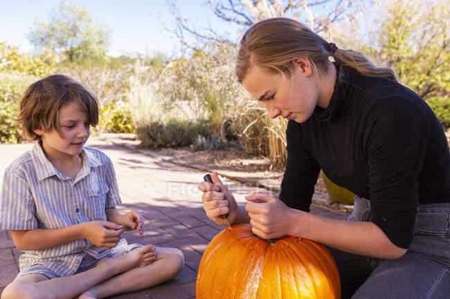 Підліток та її молодший брат вирізьблюють гарбузи на веранді.. — стокове фото