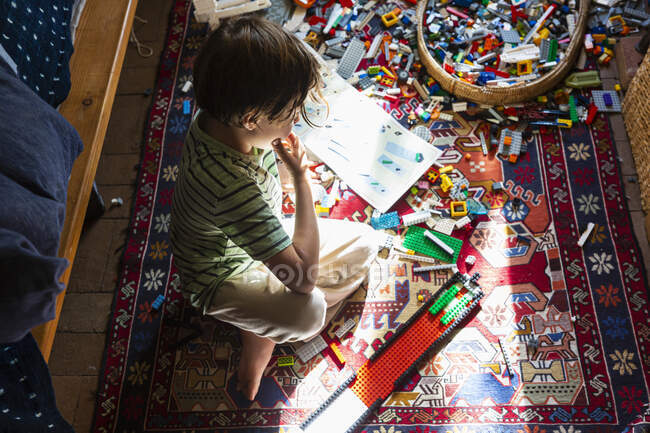 Boy sitting among toys on his bedroom floor in a patch of sunlight — Stock Photo
