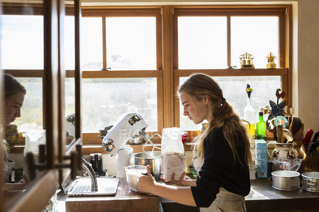 Adolescente em uma cozinha após uma receita de cozimento em um laptop. — Fotografia de Stock