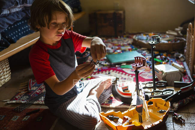 High angle view of young boy in his room playing with his toys — Stock Photo