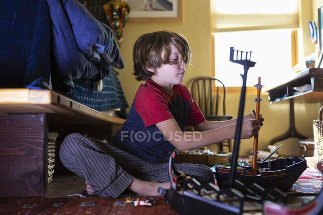 7-річний хлопчик грається з іграшками у своїй кімнаті. — стокове фото