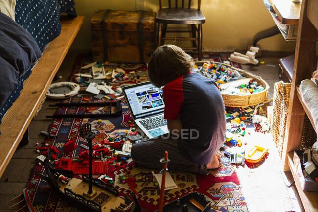 Menino brincando em seu quarto, olhando para laptop — Fotografia de Stock