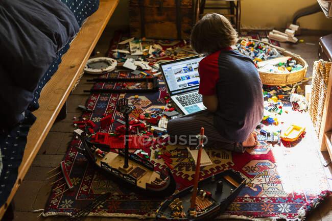 Молодий хлопчик грає в своїй кімнаті, дивлячись на ноутбук. — стокове фото