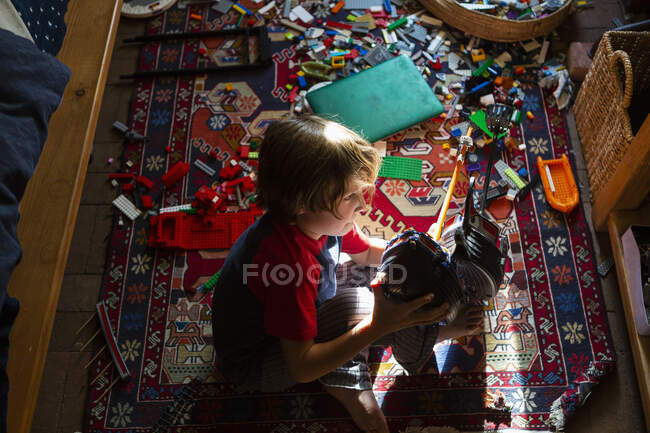 Высокий угол зрения мальчика в его комнате, играющего со своими игрушками — стоковое фото