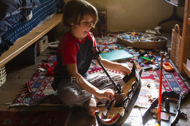 Високий кут зору молодого хлопчика в своїй кімнаті граються з його іграшками — стокове фото