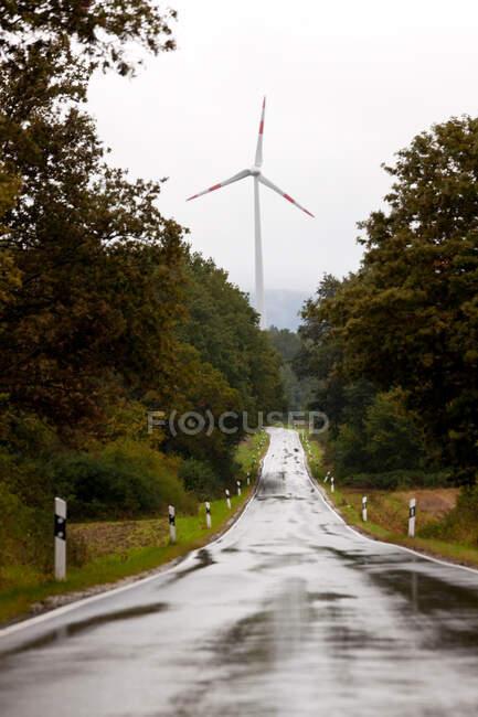 Turbina eólica y carretera recta húmeda Nr Trier, en la región vinícola de Mosela, Alemania - foto de stock