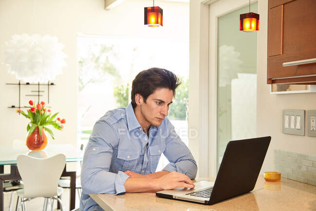 Young man using a laptop at a table, working from home. — Stock Photo