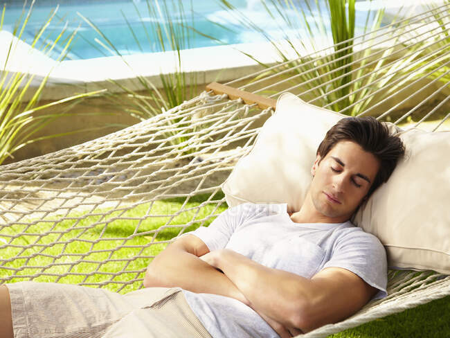 Young man sleeping in a hammock by a pool — Stock Photo