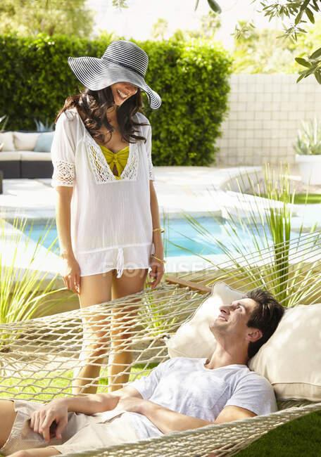 Couple heureux relaxant, femme dans un chapeau de soleil et un homme couché dans un hamac — Photo de stock