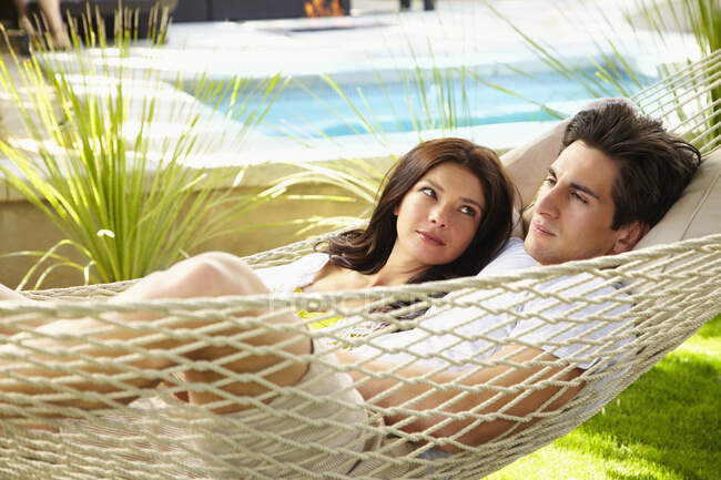 Щаслива молода пара вдома відпочиває, ділившись гамаком. — стокове фото