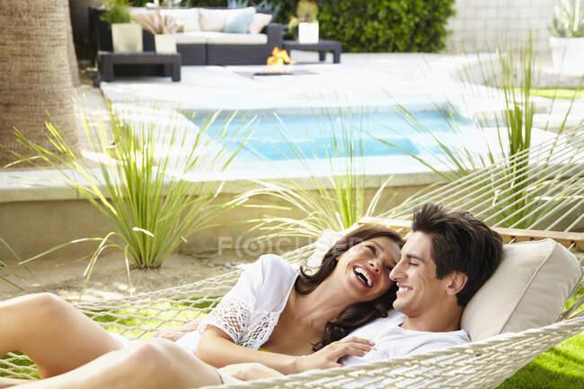 Felice giovane coppia a casa rilassante, condividendo un'amaca — Foto stock