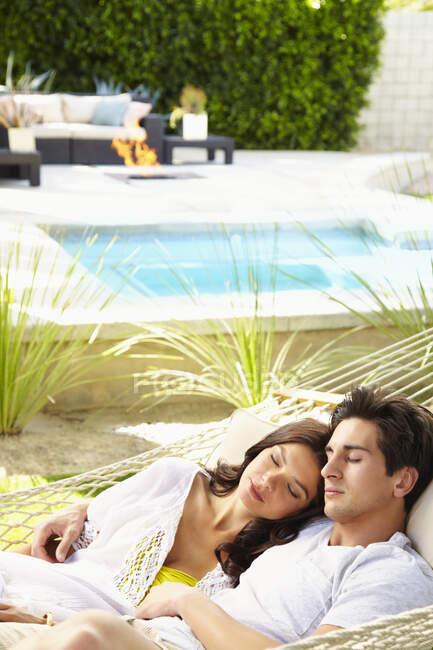 Счастливая молодая пара дома расслабляется, деля гамак — стоковое фото
