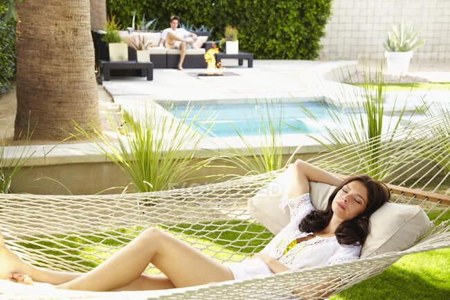 Молодая латиноамериканка в белой рубашке отдыхает в гамаке — стоковое фото