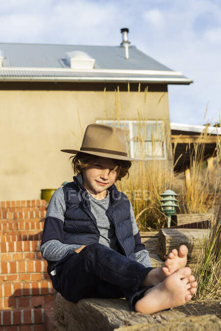 Portrait of young boy wearing fedora hat relaxing on his porch — Stock Photo