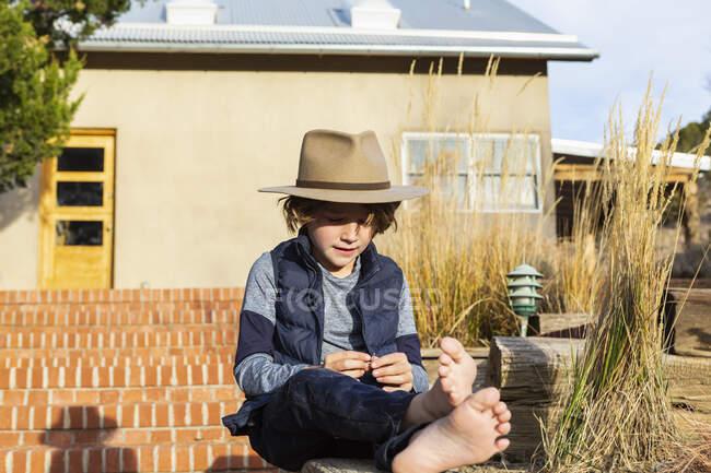 Porträt eines kleinen Jungen mit Fedora-Hut entspannt auf seiner Veranda — Stockfoto